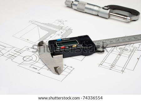 Horizontal image of a micrometer and digital caliper on a white drawing - stock photo