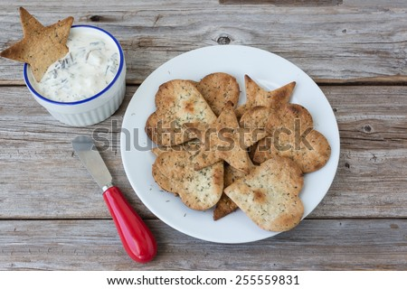 horizontal image of a plate of home made freshly baked  crispy tortilla chips with a bowl of spinach dip on the side with a little knife on a rustic wood background. - stock photo