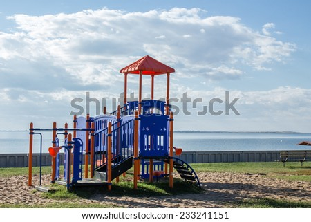 horizontal image of a play structure sitting near a big lake under a blue sky with clouds in summertime.