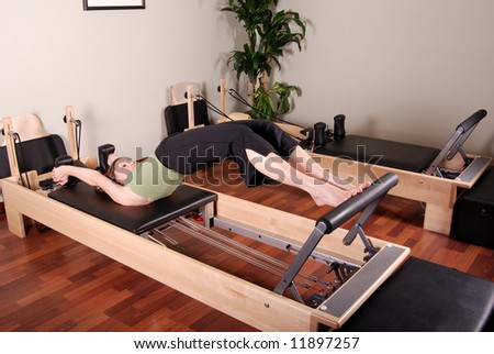 Horizontal image of a professional Pilates instructor excercising on a Reformer.