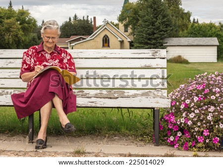 horizontal image of a smiling elderly senior citizen lady sitting on a park bench writing in a book on a summer afternoon. - stock photo