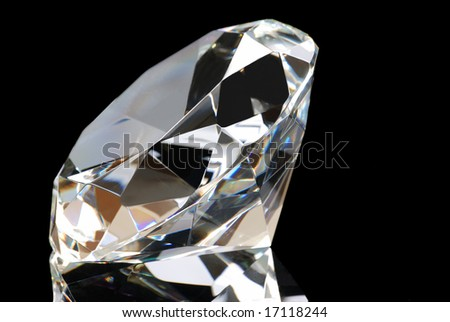 Horizontal image of a white diamond and its reflection with the table facing to the left upper corner on a black background. - stock photo