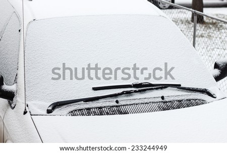 horizontal image of a windshield of a vehicle that is covered with snow in the winter time.