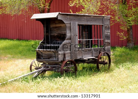 Horizontal image of an antique jail wagon against a red barn, standing beneath trees and in tall grass. - stock photo