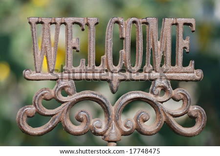 Horizontal image of an iron sign spelling out the word Welcome. - stock photo