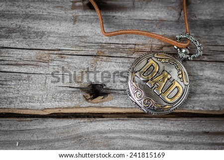 horizontal image of an old antique pocket watch with the word DAD  engraved on the lid lying on an old rustic wood background with lots of room for text - stock photo