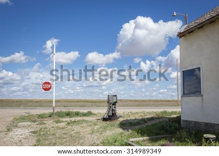 horizontal image of an old broken gas pump station sitting next to an old closed store with a stop sign at the end of the road under a beautiful blue sky with clouds in the summer time. - stock photo
