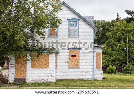 """horizontal image of an old condemned house with windows boarded up and """"no trespassing sign"""" with big tree in front in summer time  - stock photo"""