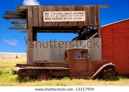 Horizontal image of an old rusted truck in front of a decaying blacksmith shop.  Old west image against a bright blue sky. - stock photo