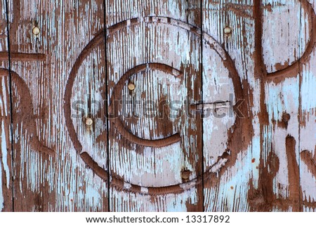 Horizontal image of an old, weathered and worn barn door with a number of brands marring it.  The copyright symbol is featured in this image. - stock photo