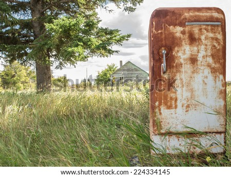horizontal image of an very old rusted fridge sitting outside in the grass in the summer time. - stock photo