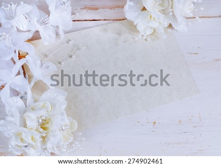 Horizontal image of blank mottled parchment paper card on rustic off-white wooden background. White and ivory colored silk flowers decorate the border of the card. Good for wedding or anniversary  - stock photo