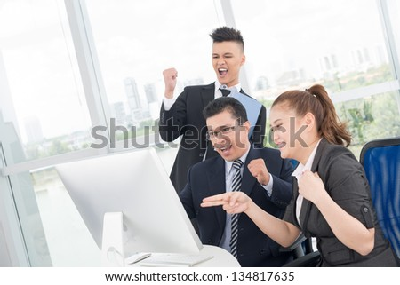 Horizontal image of cheerful businesspeople at their workplace - stock photo