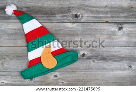 Horizontal image of Christmas elf stocking hat on rustic wooden boards - stock photo
