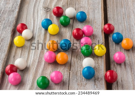 horizontal image of different coloured bubble gum scattered on an old rustic wooden background - stock photo