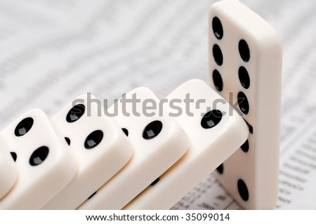 Horizontal image of falling dominoes on a newspaper stock report - stock photo