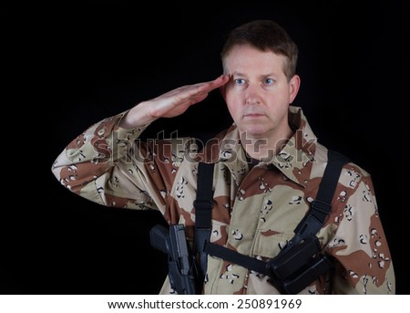 Horizontal image of military male soldier, head gear removed, saluting while armed with black background. - stock photo