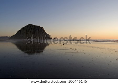 Horizontal image of Morro Rock and its reflection at sunset on Morro Beach, with copy space.