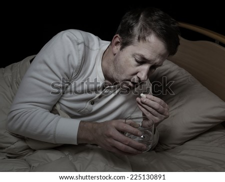 Horizontal image of sick mature man, taking medicine, while in bed  - stock photo