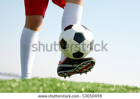 Horizontal image of soccer ball being kicked by footballer - stock photo