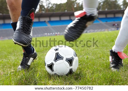 Horizontal image of soccer ball on the field with footballers legs near by - stock photo