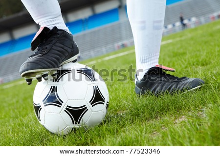 Horizontal image of soccer ball with foot of player touching it - stock photo