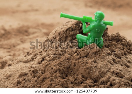 Horizontal image of soldier miniature holding a bazooka on a chocolate powder - stock photo
