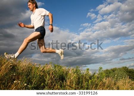Horizontal image of sport man jumping outdoor - stock photo