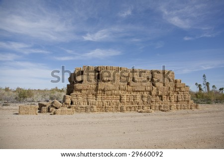 Horizontal image of stacks of bails of hay.