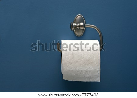 horizontal image of toilet paper on blue wall, straight on - stock photo