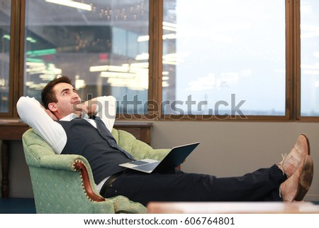 Horizontal indoors shot of adult businessman resting in the office sitting in armchair in Arlington city, Virginia.