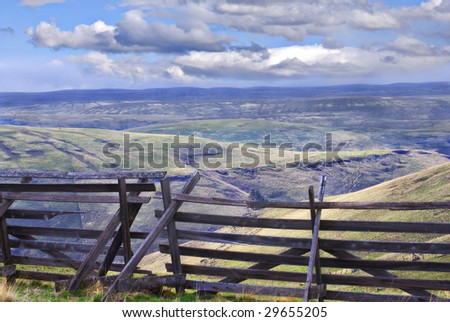 Horizontal landscape of eastern Oregon south of Pilot Rock with an old wooden snow fence in the foreground and blue cloudy skies in the background. - stock photo