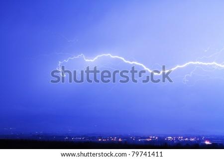 Horizontal lightning bolt striking over city lights - stock photo