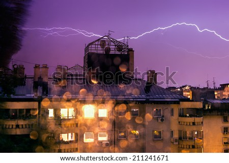 Horizontal lightning, night storm in the city with bokeh - stock photo