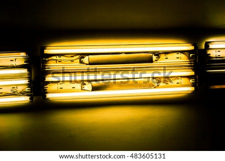 horizontal long lamp against dark background, horizontal lamps divided into sections with lights against dark background, high quality resolution, ceiling office lamp with light
