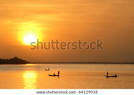Horizontal of African fishermen in canoes at sunset - stock photo