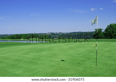 Horizontal of golf green with flag in hole pond in background