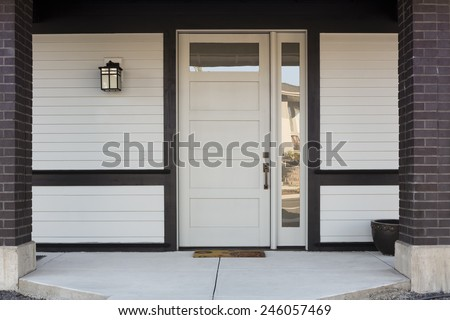 Horizontal of White And Black Front Entryway with White Siding, a White Front Door, and Black Framing - stock photo