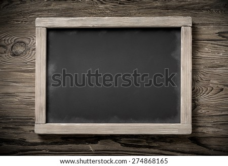 horizontal old chalkboard on dark aged wood background,desaturated image - stock photo