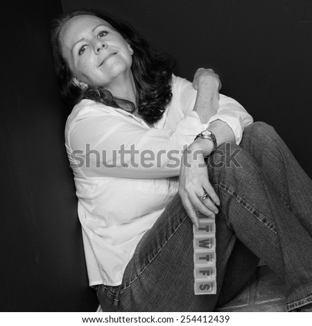 horizontal orientation black and white image of an attractive, smiling woman, sitting on the floor with a pill box / Improving health through Medication - stock photo
