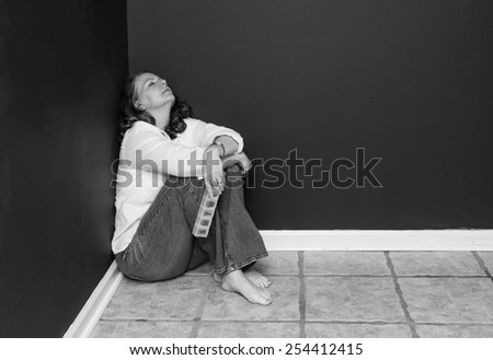 horizontal orientation black and white image of an attractive, tired woman, in the corner of a dark room, with a pill box / Finding the right Medication - stock photo