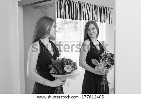 horizontal orientation black and white image of an older teenage girl checking the fit of her formal dress in the mirror as she holds a bouquet / Dressing for the Event - stock photo