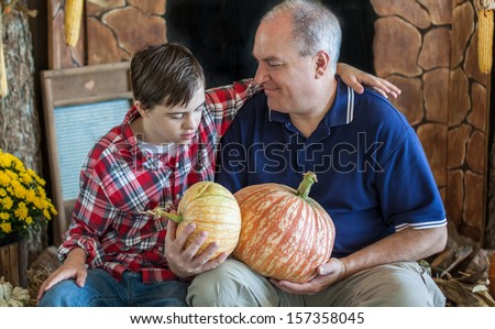 horizontal orientation close up of a boy with autism and down's syndrome and his smiling Dad, seated together holding pumpkins with copy space / Father and Son Choose Pumpkins - stock photo