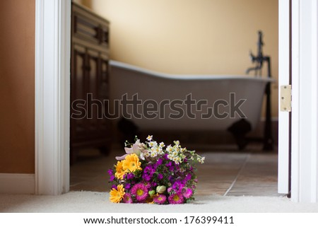 horizontal orientation close up of a bright bouquet in the foreground and deep, claw foot tub in an updated bathroom in the background with copy space / Updating your Bathroom - stock photo