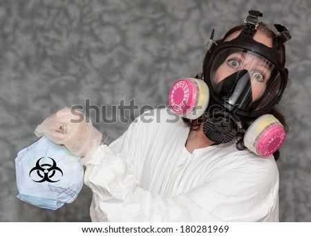 horizontal orientation close up of a woman dressed in a lab coat and gloves with a filtered gas mask on, holding a stinky diaper with a bio hazard symbol / Disgusting Diaper - stock photo
