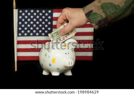 horizontal orientation close up of a woman's arm and hand in camouflage uniform putting cash in a piggy bank, with the U.S. flag in the background on isolated black / Saving while Serving - Horizontal - stock photo