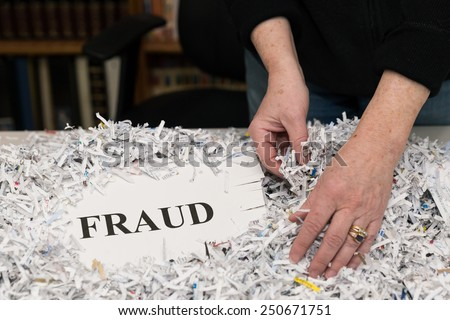 horizontal orientation close up of a woman's hands gathering shredded paper to recycle with the word FRAUD shown / Preventing Fraud - stock photo