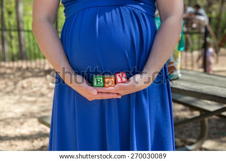 horizontal orientation close up of an expectant mother, dressed in bright blue, holding blocks that say BOY /  Torso of a Mother expecting a baby BOY - stock photo