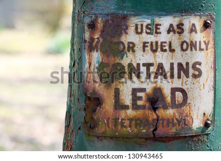 horizontal orientation close up of motor fuel sign with rusted out letters and greenish background with copy space / Fully Leaded - stock photo