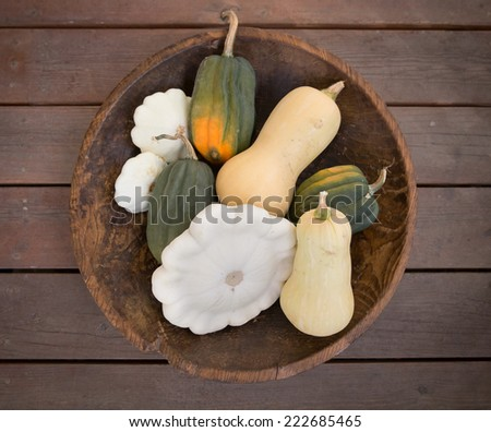 horizontal orientation close up of several different types of squash, neatly arranged in a wooden bowl, with neutral background / Squash Varieties - stock photo